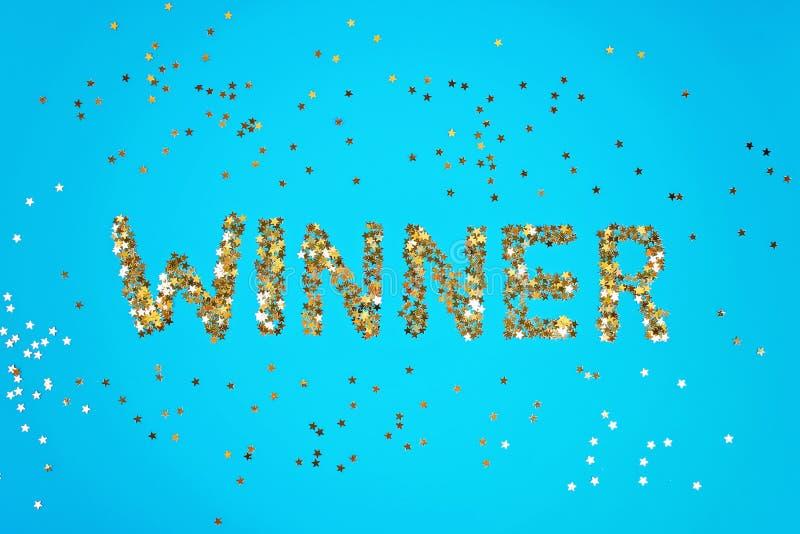Ο νικητής λέξης σχεδιάζεται του έναστρου κομφετί σε ένα μπλε υπόβαθρο στοκ φωτογραφία με δικαίωμα ελεύθερης χρήσης