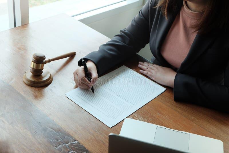 Ο νομικός σύμβουλος παρουσιάζει στον πελάτη μια υπογεγραμμένη σύμβαση με gavel και το νομικό νόμο στοκ εικόνες