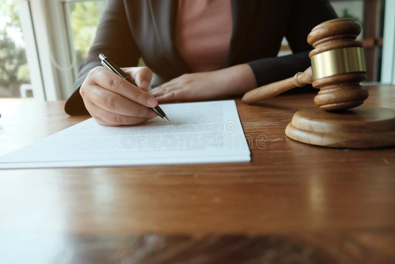 Ο νομικός σύμβουλος παρουσιάζει στον πελάτη μια υπογεγραμμένη σύμβαση με gavel και το νομικό νόμο στοκ εικόνα με δικαίωμα ελεύθερης χρήσης