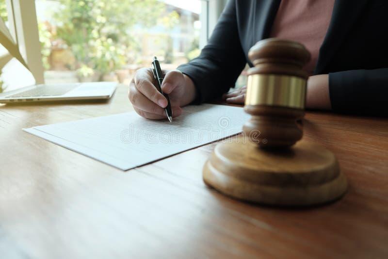 Ο νομικός σύμβουλος παρουσιάζει στον πελάτη μια υπογεγραμμένη σύμβαση με gavel και το νομικό νόμο στοκ φωτογραφίες με δικαίωμα ελεύθερης χρήσης