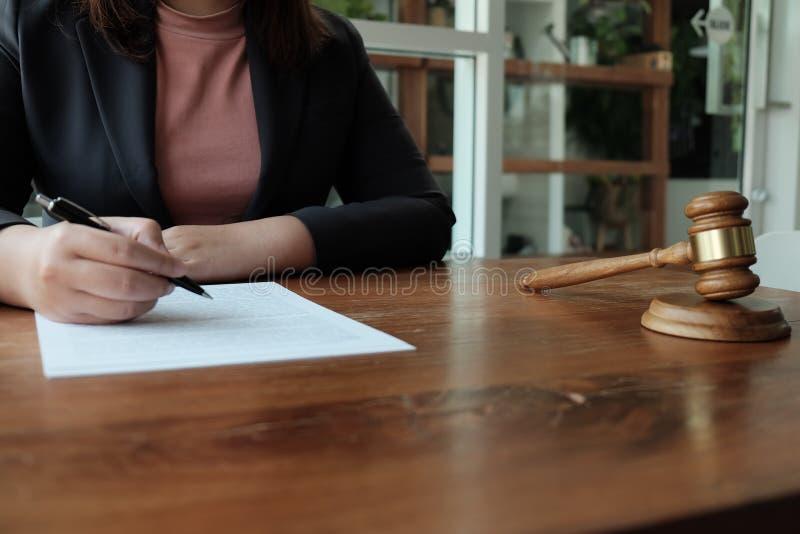 Ο νομικός σύμβουλος παρουσιάζει στον πελάτη μια υπογεγραμμένη σύμβαση με gavel και το νομικό νόμο δικαιοσύνη και νόμος δικηγόρων  στοκ εικόνα