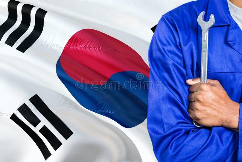 Ο νοτιοκορεατικός μηχανικός μπλε σε ομοιόμορφο κρατά το γαλλικό κλειδί στο κυματίζοντας κλίμα σημαιών της Νότιας Κορέας Διασχισμέ στοκ φωτογραφίες