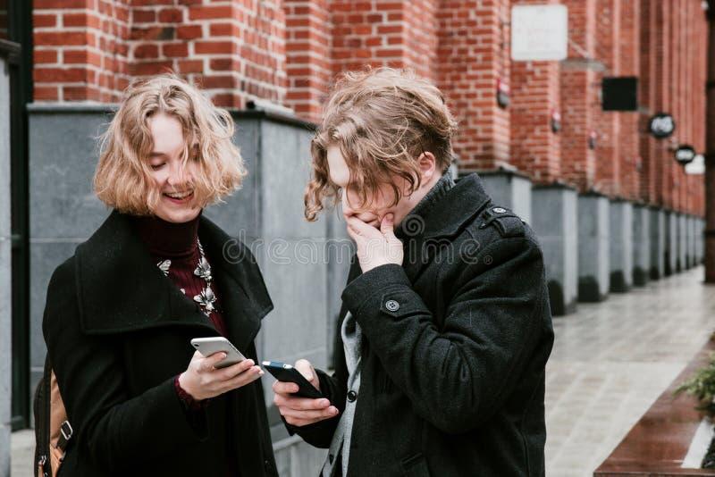 Ο ξανθός σγουρός-μαλλιαρός τύπος και το ίδιο κορίτσι ψάχνουν τις πληροφορίες στις κινητές συσκευές στοκ εικόνα με δικαίωμα ελεύθερης χρήσης