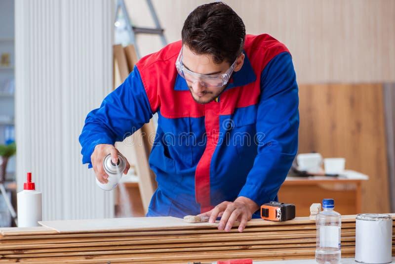 Ο ξυλουργός επισκευαστών yooung που εργάζεται με τη ζωγραφική χρωμάτων στοκ εικόνες