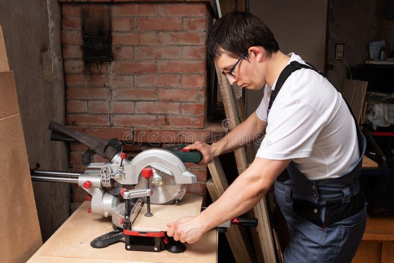Ο ξυλουργός κόβει ένα κομμάτι του κοντραπλακέ με ένα miter πριόνι στοκ φωτογραφίες με δικαίωμα ελεύθερης χρήσης