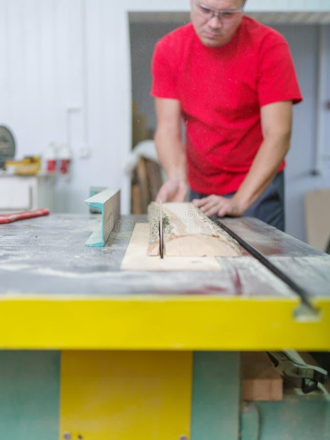 Ο ξυλουργός πριονίζει την ακτίνα ξυλείας σε ένα κυκλικό πριόνι στοκ εικόνα