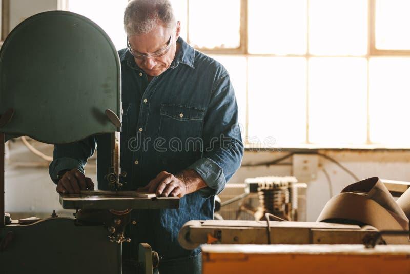 Ο ξυλουργός στο εργαστήριο κόβει το ξύλινο χρησιμοποιώντας πριόνι ζωνών στοκ εικόνες