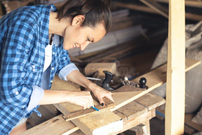 Ο ξυλουργός συμμετέχει στην εργασία σε ένα εγχώριο εργαστήριο στοκ φωτογραφία με δικαίωμα ελεύθερης χρήσης