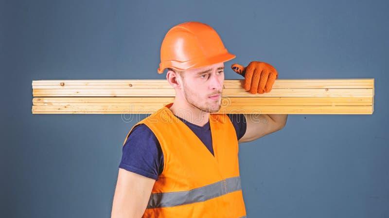 Ο ξυλουργός, woodworker, ισχυρός οικοδόμος στο σοβαρό πρόσωπο φέρνει την ξύλινη ακτίνα στον ώμο Άτομο στο κράνος, σκληρό καπέλο κ στοκ εικόνα με δικαίωμα ελεύθερης χρήσης