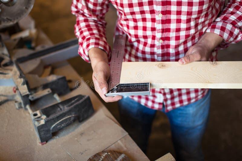 Ο ξυλουργός μετρά το πάχος πινάκων της γωνίας, s του ξυλουργού στοκ φωτογραφία με δικαίωμα ελεύθερης χρήσης