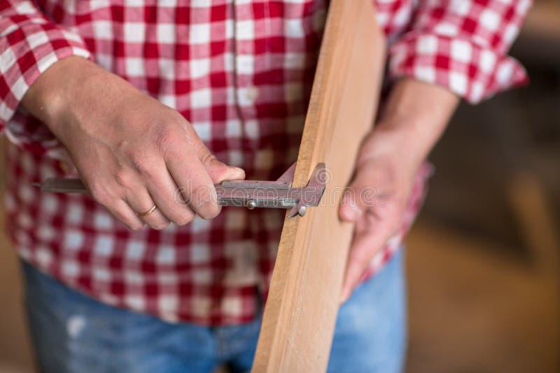 Ο ξυλουργός μετρά το πάχος πινάκων των παχυμετρικών διαβητών, joiner στοκ εικόνα με δικαίωμα ελεύθερης χρήσης