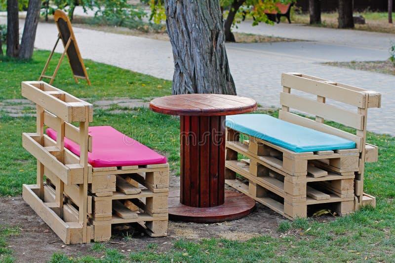 Ο ξύλινος πάγκος φιαγμένος από παλέτες για το κάθισμα με τον πίνακα έκανε από τη σπείρα του ηλεκτρικού καλωδίου στοκ φωτογραφίες με δικαίωμα ελεύθερης χρήσης