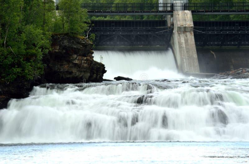 Ο ογκώδης άσπρος καταρράκτης κάτω από τους βράχους ως εγκαταστάσεις υδραυλικής ισχύος ανοίγει το τσιμεντένιο φράγμα στοκ φωτογραφίες