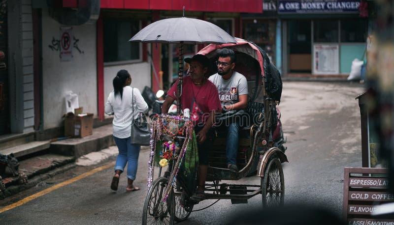 Ο οδηγός δίτροχων χειραμαξών φέρνει τον επιβάτη που περνά την οδό Thamel στοκ φωτογραφίες με δικαίωμα ελεύθερης χρήσης