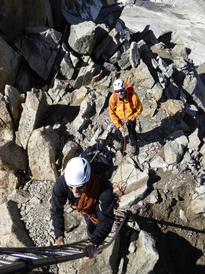 Ο οδηγός και ο πελάτης βουνών παίρνουν έτοιμοι να αναρριχηθούν σε μια σκάλα στην έξοδο της διαδρομής αναρρίχησής τους σε Chamonix στοκ εικόνα με δικαίωμα ελεύθερης χρήσης