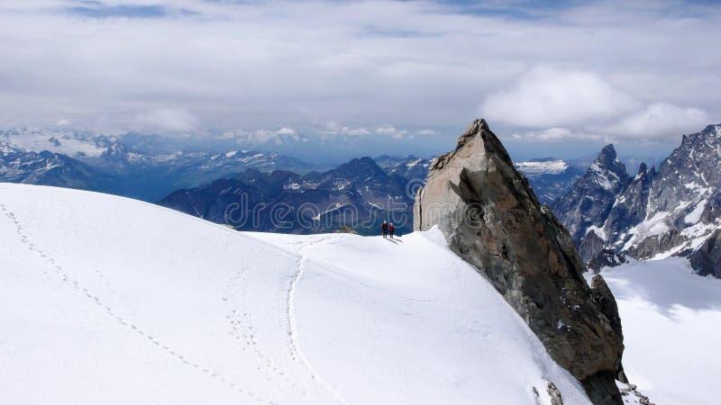 Ο οδηγός και ο πελάτης βουνών περπατούν κατά μήκος μιας στενής κορυφογραμμής χιονιού με μια γιγαντιαία βελόνα βράχου και μιας φαν στοκ φωτογραφία