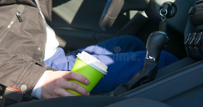 Ο οδηγός, που κάθεται πίσω από τη ρόδα ενός αυτοκινήτου, που κρατά ένα ποτό ενδυνάμωσης του καφέ, κινηματογράφηση σε πρώτο πλάνο στοκ εικόνες
