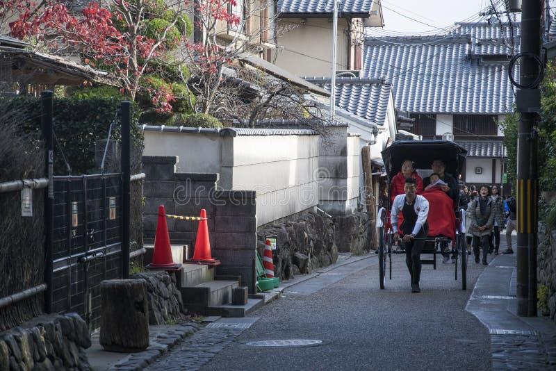 Ο οδηγός Rickshaw με τους πελάτες του οδηγεί στο δρόμο στο Arashiyama, Κιότο στοκ φωτογραφίες