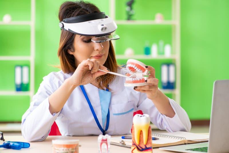 Ο οδοντίατρος γυναικών που εργάζεται στο μόσχευμα δοντιών στοκ φωτογραφία