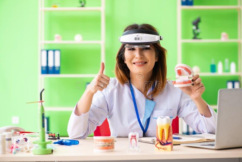 Ο οδοντίατρος γυναικών που εργάζεται στο μόσχευμα δοντιών στοκ εικόνες