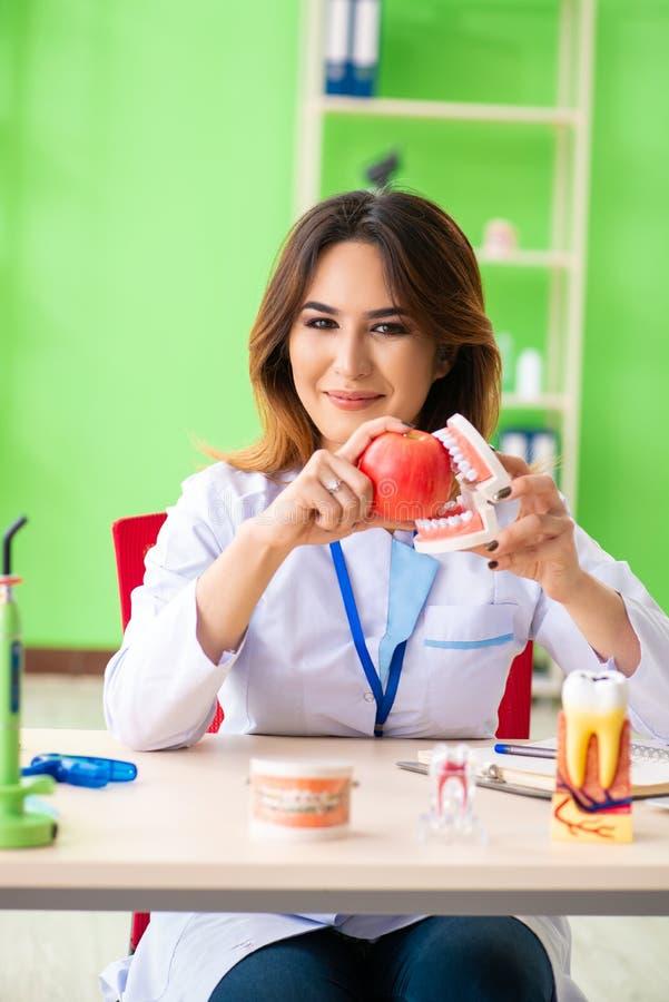 Ο οδοντίατρος γυναικών που εργάζεται στο μόσχευμα δοντιών στοκ εικόνα