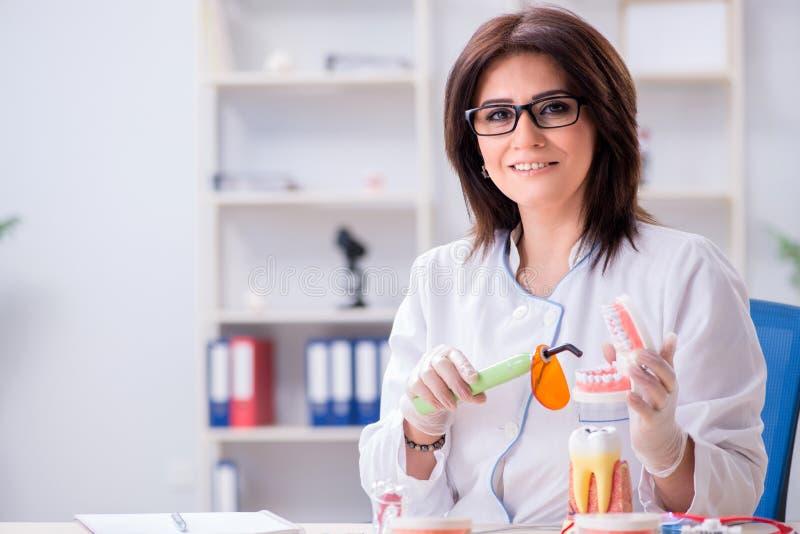 Ο οδοντίατρος γυναικών που εργάζεται στο μόσχευμα δοντιών στοκ φωτογραφίες με δικαίωμα ελεύθερης χρήσης