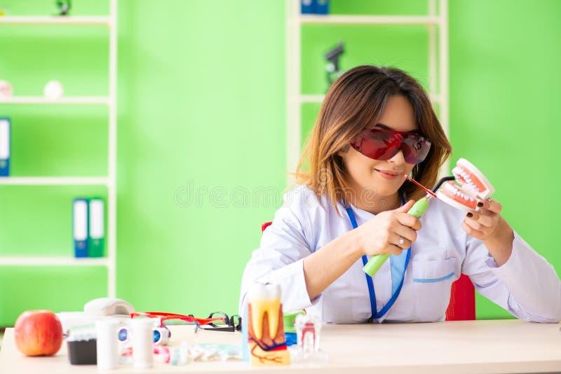 Ο οδοντίατρος γυναικών που εργάζεται στο μόσχευμα δοντιών στοκ φωτογραφία με δικαίωμα ελεύθερης χρήσης