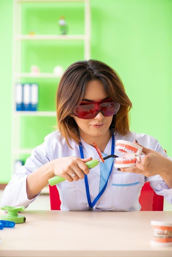 Ο οδοντίατρος γυναικών που εργάζεται στο μόσχευμα δοντιών στοκ φωτογραφίες