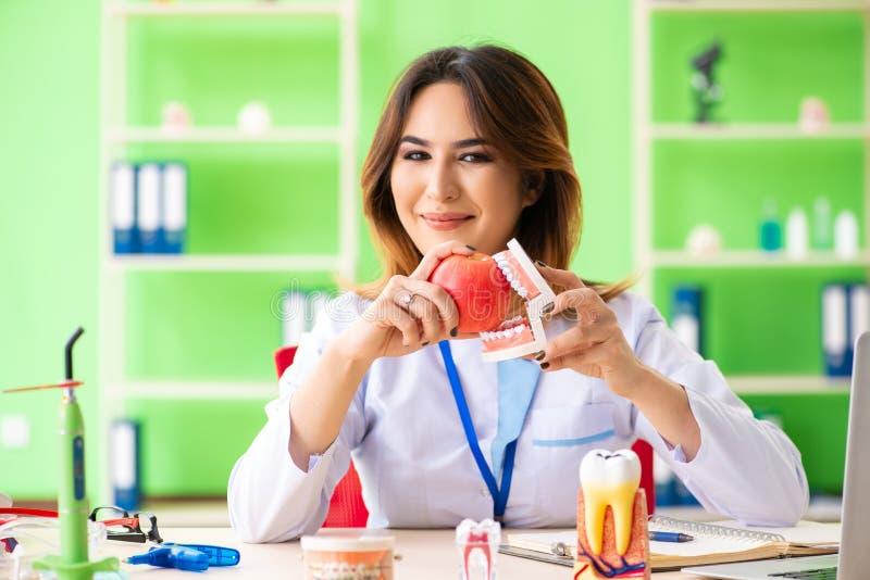Ο οδοντίατρος γυναικών που εργάζεται στο μόσχευμα δοντιών στοκ εικόνα με δικαίωμα ελεύθερης χρήσης