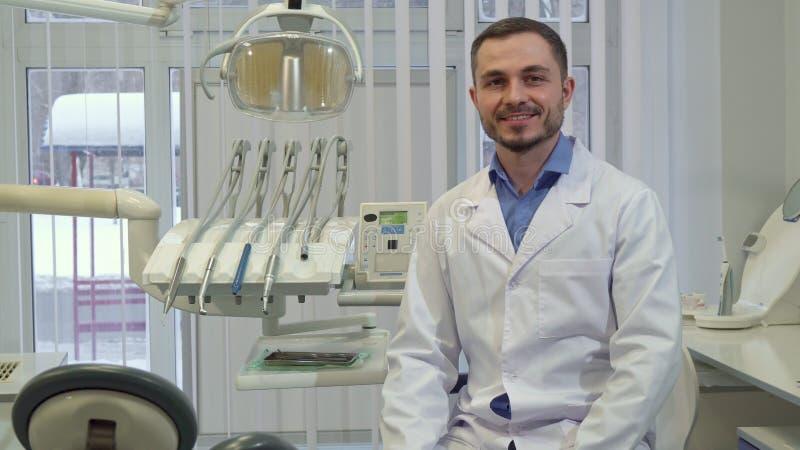 Ο οδοντίατρος κάθεται στην καρέκλα στο γραφείο του στοκ εικόνα