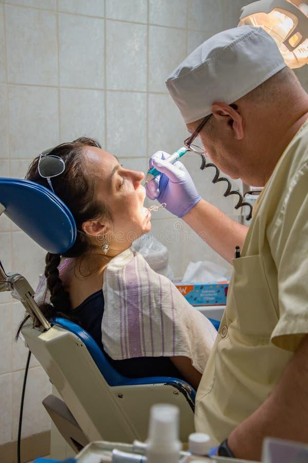 Ο οδοντίατρος μεταχειρίζεται τα δόντια μιας γυναίκας, ιδιωτική οδοντική κλινική, ανώδυνη προσθετική στον οδοντίατρο στοκ φωτογραφία