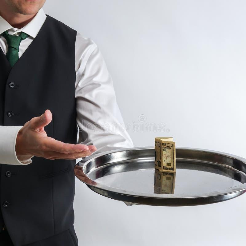 Ο οικονόμος/ο σερβιτόρος κρατά έναν ασημένιο δίσκο με έναν λογαριασμό δέκα δολαρίων στοκ εικόνα με δικαίωμα ελεύθερης χρήσης