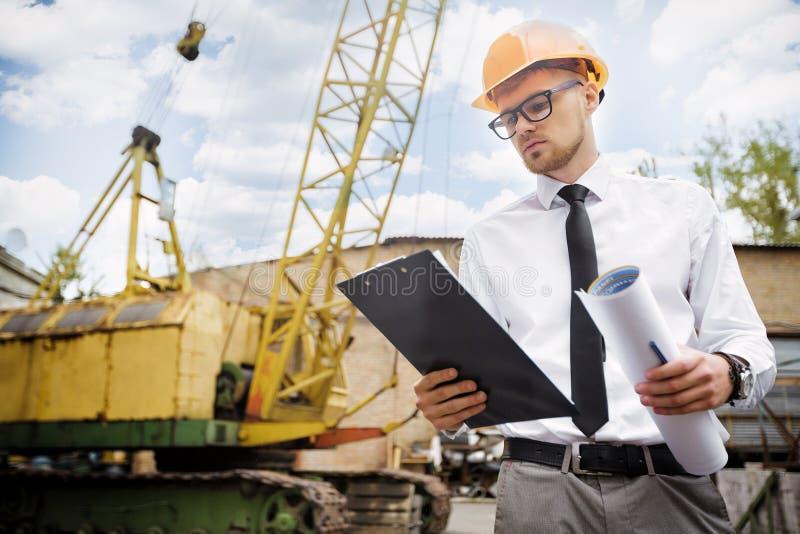 Ο οικοδόμος μηχανικών σε ένα κράνος κρατά τα σχέδια στο εργοτάξιο οικοδομής στοκ φωτογραφίες με δικαίωμα ελεύθερης χρήσης