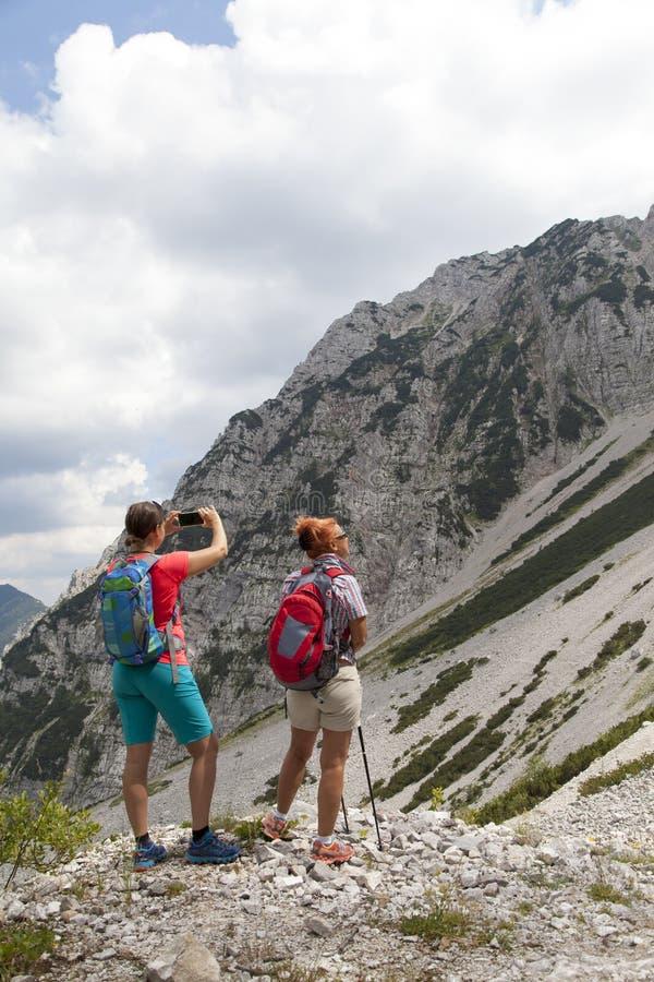 Οδοιπόροι που περπατούν στο πεζοπορώ στο τοπίο φύσης βουνών και που παίρνουν τις φωτογραφίες στοκ εικόνες με δικαίωμα ελεύθερης χρήσης