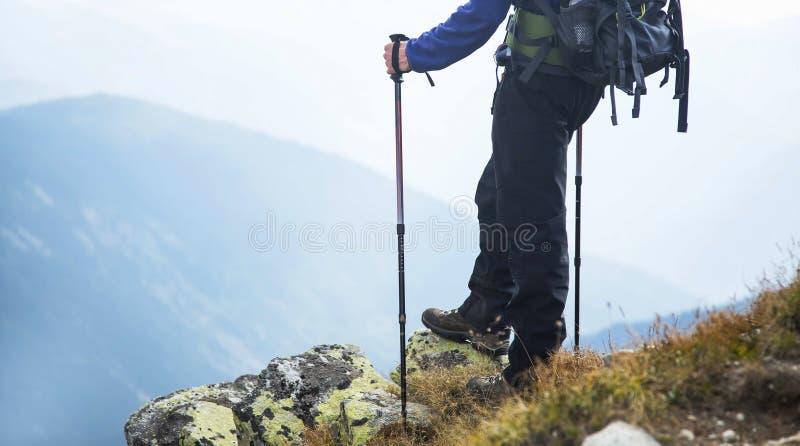Οδοιπόρος σε έναν βράχο πάνω από το βουνό με τα ραβδιά οδοιπορίας και πίσω στοκ εικόνα με δικαίωμα ελεύθερης χρήσης