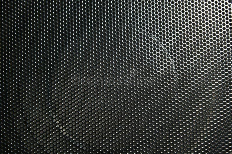 Ο ομιλητής μιας μουσικής στήλης που κρύβεται πίσω από ένα πλέγμα με ένα σχέδιο των ρυθμικά τακτοποιημένων τρυπών στοκ φωτογραφίες