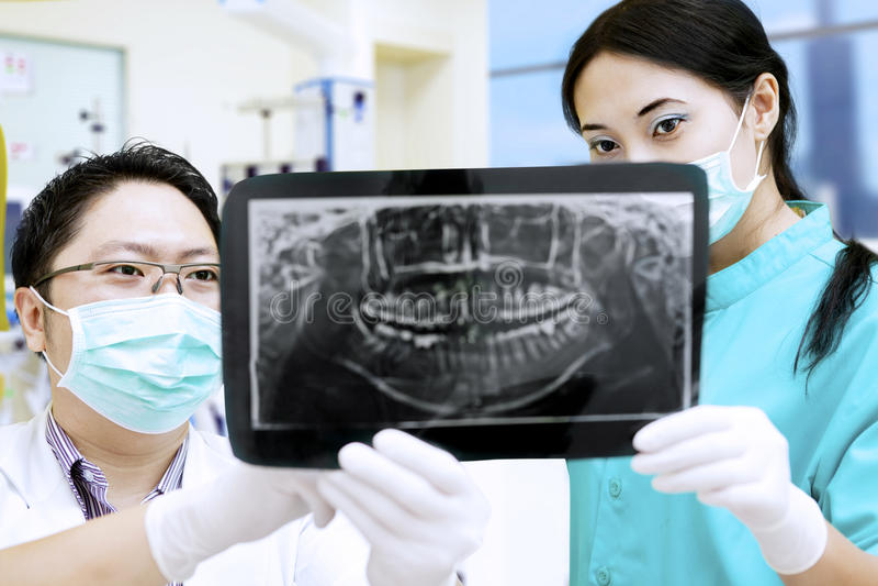 Οδοντίατρος και βοηθός που αναλύουν την ακτίνα X στην οδοντική κλινική στοκ φωτογραφία με δικαίωμα ελεύθερης χρήσης