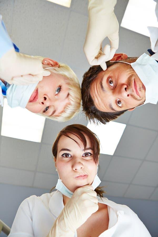 Οδοντίατρος και οδοντικοί βοηθοί που φαίνονται σκεπτικοί στοκ φωτογραφία