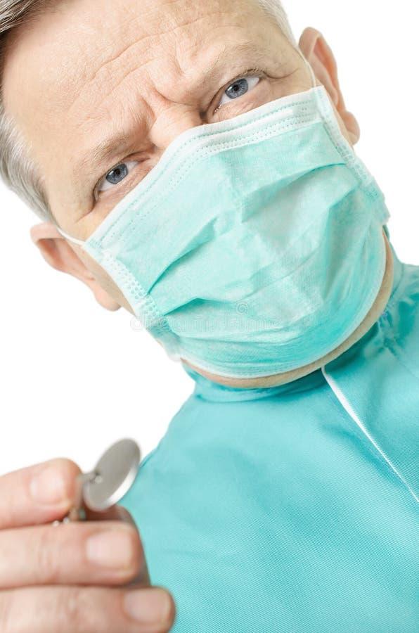 Οδοντίατρος με έναν καθρέφτη που εξετάζει τη κάμερα στοκ φωτογραφία