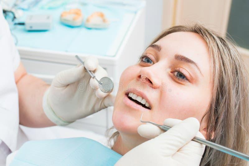 Οδοντίατρος που εξετάζει το τα υπομονετικά δόντια ` s, όμορφο πορτρέτο κινηματογραφήσεων σε πρώτο πλάνο γυναικών κατά τη διάρκεια στοκ εικόνες
