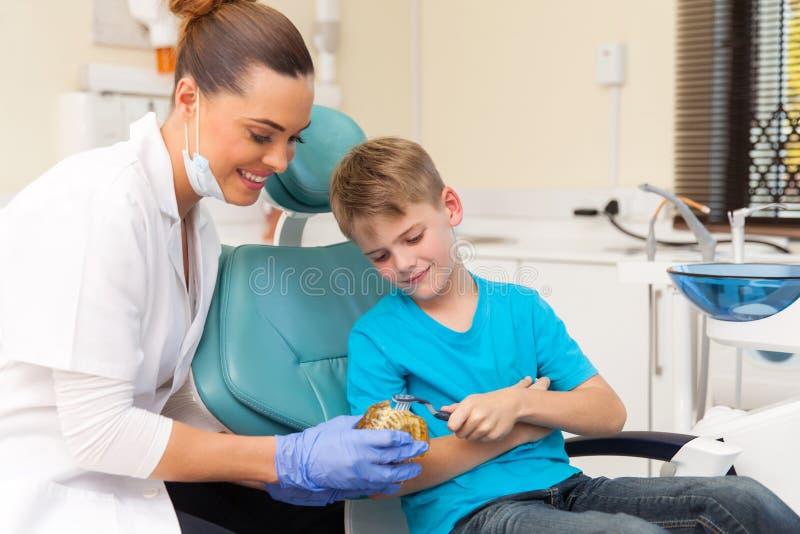 Οδοντίατρος που διδάσκει το νέο αγόρι στοκ εικόνες