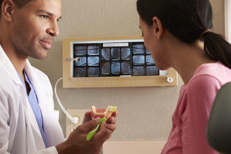 Οδοντίατρος που καταδεικνύει πώς να βουρτσίσει τα δόντια στο θηλυκό ασθενή στοκ φωτογραφία με δικαίωμα ελεύθερης χρήσης