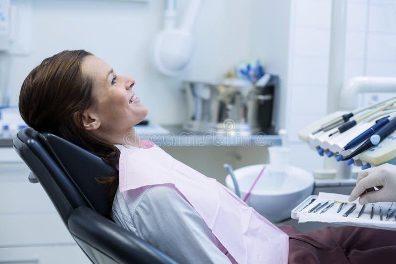 Οδοντίατρος που παίρνει τα οδοντικά εργαλεία για να εξετάσει έναν θηλυκό ασθενή στοκ φωτογραφία