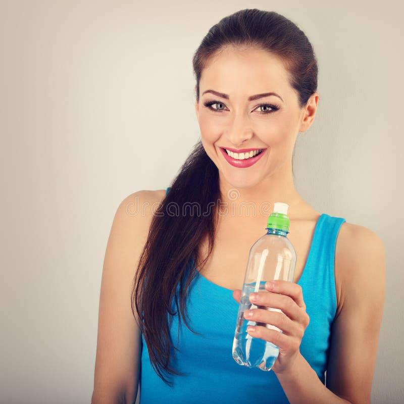 Οδοντωτή χαμογελώντας ευτυχής όμορφη γυναίκα που κρατά το μπουκάλι καθαρού στοκ φωτογραφίες με δικαίωμα ελεύθερης χρήσης