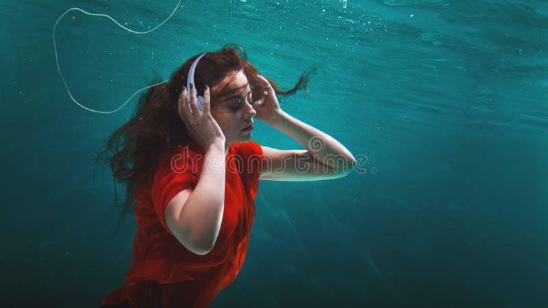 Ο οπαδός μουσικής κοριτσιών απολαμβάνει τη μουσική, η έννοια Βαθύς βουτήξτε στοκ φωτογραφία