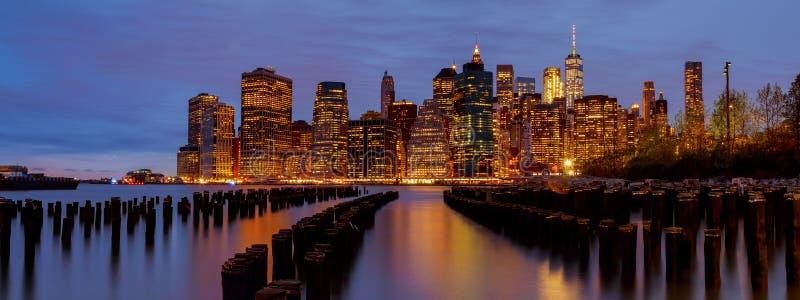 Ο ορίζοντας του Μανχάταν πόλεων της Νέας Υόρκης με τους ουρανοξύστες πέρα από τον ποταμό του Hudson φώτισε τα φω'τα στο σούρουπο  στοκ εικόνες