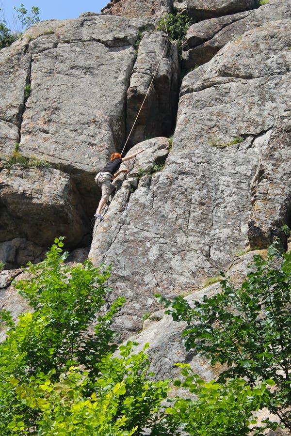 Ο ορειβάτης βράχου γυναικών αναρριχείται σε έναν βράχο στοκ εικόνα