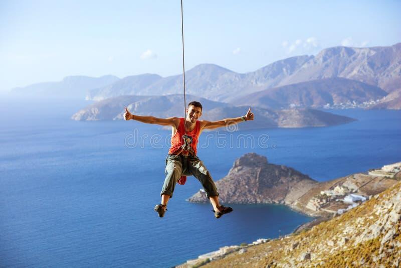 Ο ορειβάτης βράχου που ταλαντεύεται στο σχοινί και που παρουσιάζει φυλλομετρεί επάνω στοκ φωτογραφίες