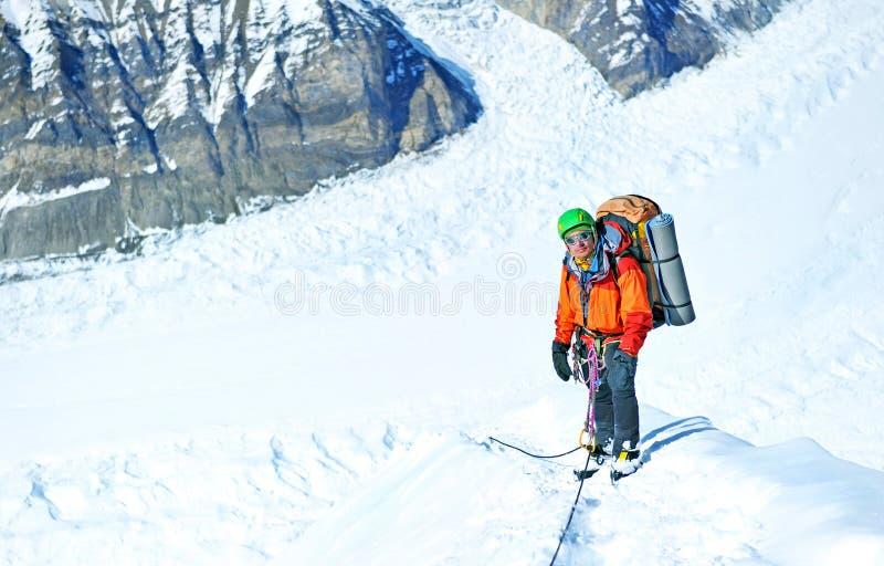 Ο ορειβάτης φθάνει στην κορυφή της αιχμής βουνών Επιτυχία, ελευθερία και ευτυχία, επίτευγμα στα βουνά Αναρρίχηση της αθλητικής έν στοκ εικόνα με δικαίωμα ελεύθερης χρήσης