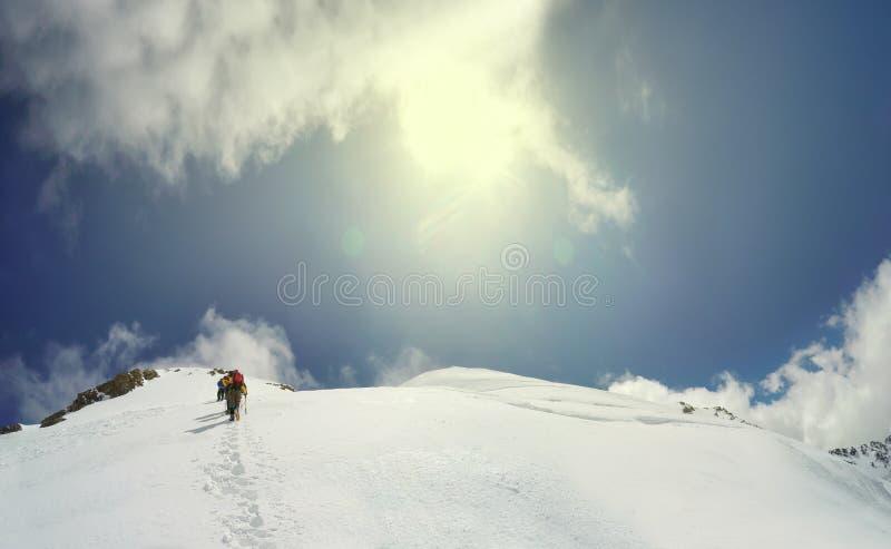 Ο ορειβάτης φθάνει στην κορυφή της αιχμής βουνών στοκ εικόνα